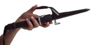 Hand som rymmer ett krullande hårhjälpmedel Arkivbilder