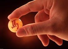 Hand som rymmer ett stycke av kinesiskt schack Arkivfoton