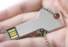Hand som rymmer ett tangent format USB drev Arkivbild