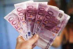 Hand som rymmer 500 euroanmärkningar Fotografering för Bildbyråer