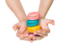 Hand som rymmer färgrika macarons Fotografering för Bildbyråer