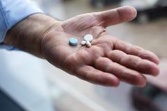 hand som rymmer gammala pills Arkivfoto