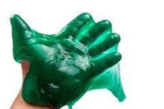 Hand som rymmer grön slam isolerad på vitt fotografering för bildbyråer
