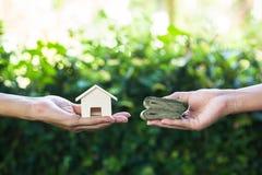 Hand som rymmer hem- modelländring till pengar med den gröna naturen som lodisar royaltyfri foto