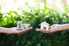 Hand som rymmer hem- modelländring till pengar med den gröna naturen som lodisar royaltyfri fotografi