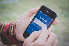Hand som rymmer Iphone och använder den Facebook applikationen royaltyfri fotografi
