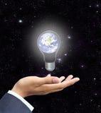 Hand som rymmer jord för ljus kula (jordsiktsbilden fr Arkivfoto