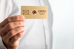 Hand som rymmer litet papper med kontaktsymboler Arkivbilder