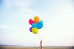 Hand som rymmer mångfärgade ballonger Royaltyfri Foto