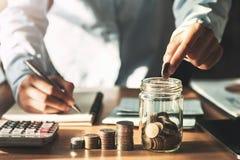 hand som rymmer mynt som sätter in i tillbringareexponeringsglas för sparande pengar begreppsfinans royaltyfria foton