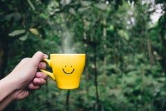 Hand som rymmer på den varma gula kaffekoppen med den hand drog leendeframsidan Royaltyfria Bilder