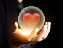 Hand som rymmer röd hjärta i kristallkula Fotografering för Bildbyråer