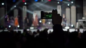 Hand som rymmer rekord- folk för dans för konturer för musikband för videokameraSmartphone Live Concert Performance Taking Photo  arkivfilmer