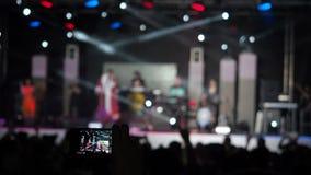 Hand som rymmer rekord- folk för dans för konturer för musikband för videokameraSmartphone Live Concert Performance Taking Photo  stock video