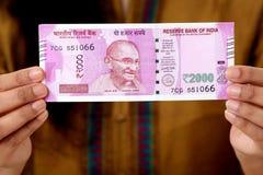 Hand som rymmer 2000 rupieanmärkning Arkivfoto