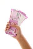 Hand som rymmer 2000 rupieanmärkningar mot vit Arkivfoton