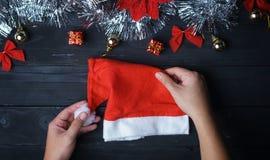 Hand som rymmer Santa Hat Försilvra julprydnaden på svart trä royaltyfri foto