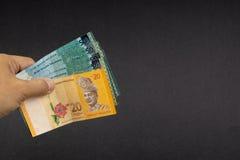 Hand som rymmer sedlar f?r valuta f?r Malaysia RinggitMYR arkivbilder