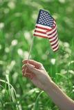 Hand som rymmer USA-flaggan för självständighetsdagen fotografering för bildbyråer
