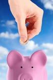 Hand som sätter en mynta in i piggy, packar ihop Royaltyfri Fotografi