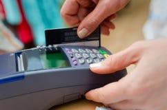 Hand som sätter kreditkorten in i betalning, bearbetar med maskin Arkivbild