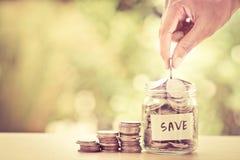 Hand som sätter mynt i den glass kruset för pengar som sparar finansiell conce arkivfoto