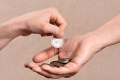 Hand som sätter mynt i gömma i handflatan av en annan person, closeup Royaltyfria Foton