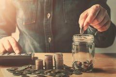 hand som sätter mynt in i tillbringareexponeringsglas för sparande finans och redovisa för pengar royaltyfria bilder