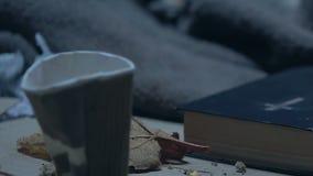 Hand som sätter myntet in i den smutsiga koppen, bibel som ligger nära tiggaren, religiösa välgörenheter stock video