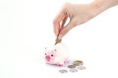 Hand som sätter pengar i en spargris Royaltyfri Foto