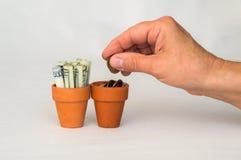 Hand som sätter pengarmynt i en terrakottakruka Arkivfoto