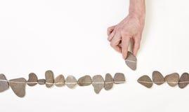 Hand som sätter stenen fodrar in Arkivfoto