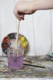 Hand som sköljer målarpenseln i krus av vatten Royaltyfri Foto