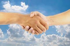 Hand som skakar på bakgrund för blå himmel arkivbilder