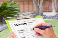 Hand som skriver en Estimate för trädgårds- underhåll royaltyfri foto