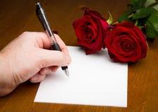 Hand som skriver en förälskelse Valentine Letter With Roses Royaltyfri Bild