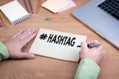 Hand som skriver Hashtag Kontorsskrivbord med en bärbar dator och en brevpapper Arkivbilder