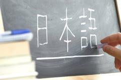 Hand som skriver några ordet & x22en; Japanese& x22; i kanasyllabary på en svart tavla i en japansk grupp Royaltyfri Foto