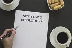 Hand som skriver upplösningar för ` s för nytt år, två kaffekoppar och en bunke av kakor Arkivbilder