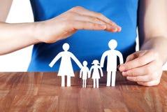 Hand som skyddar en familj Arkivbild