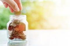 Hand som sparar ett mynt in i den glass kruset på suddigt grönt naturligt b royaltyfri foto