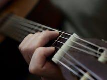 Hand som spelar ackordet på den akustiska gitarren royaltyfria foton