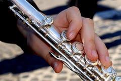 Hand som spelar en tvärflöjt arkivfoto