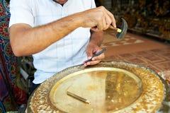 Hand som stämplar eller inristar metallmodellen Arkivbild