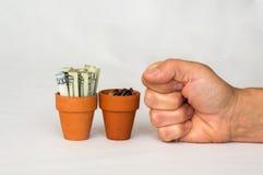 Hand som stansar pengar i terrakottakrukor Royaltyfri Fotografi