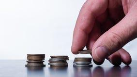 Hand som staplar små mynt på en tabell arkivbild