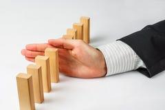 Hand som stoppar att falla för domino Arkivfoto