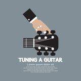 Hand som trimmar en gitarr Arkivfoto