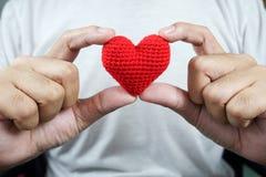 Hand som två rymmer röd hjärta Arkivbild