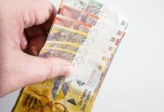 Hand som upp väljer en bunt av schweizaren Franc Notes Arkivbild